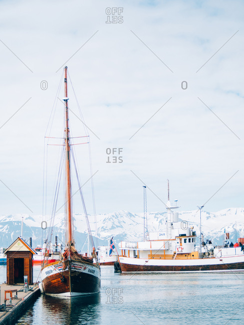 Iceland - June 3, 2016: The boats parked near the pier in snowy mountains.
