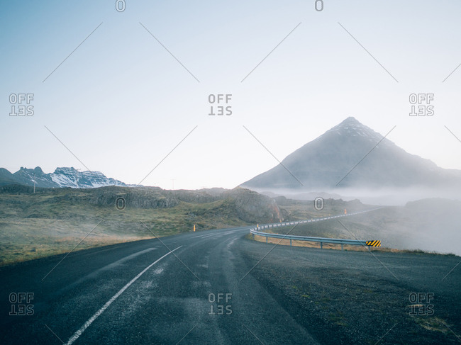 A road to the mountain with the fog on it.