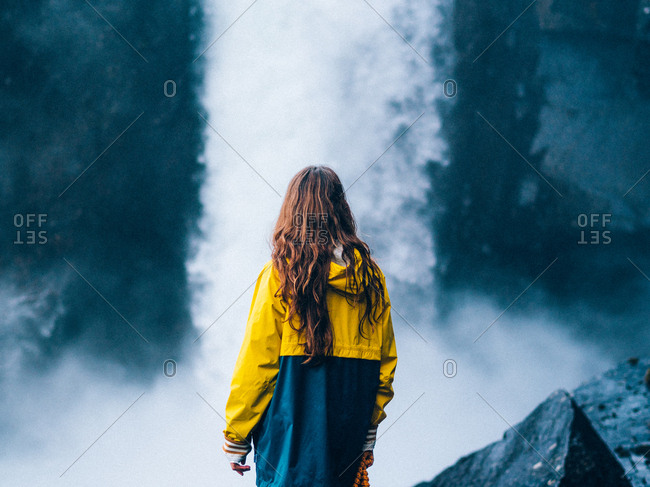 Woman in bright yellow jacket standing against powerful waterfall