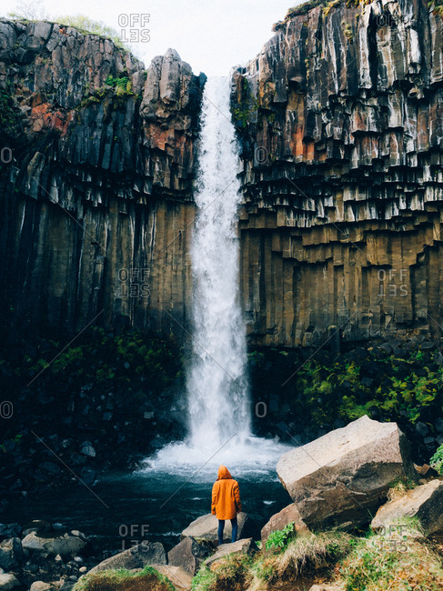 Person in orange jacket standing against powerful waterfall