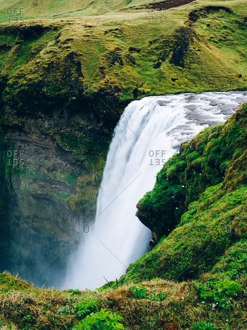 View to river and waterfall in the mountain meadow. Vertical outdoors shot,
