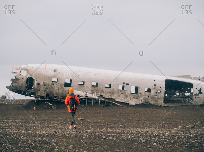 Woman walking alone against old plane wreckage