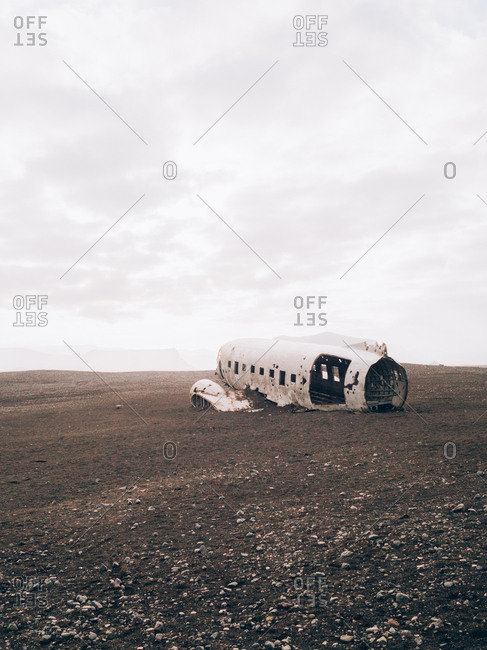A broken airplane body lying on the empty ground.