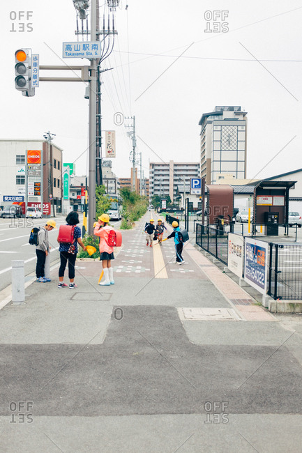 Japan - September 16, 2015: People waiting the traffic light while children playing on a sidewalk.