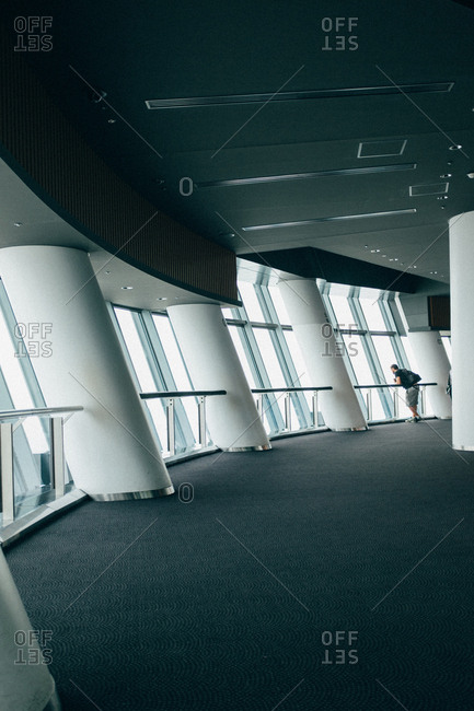 A person inside the futuristic building looking at the window.