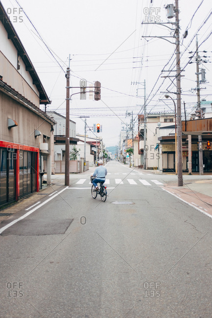 Japan - September 15, 2015: Back view of a person riding to the crossroad on his bike.