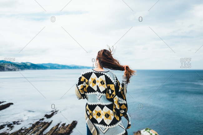 Back view of woman with flying hair standing on the edge and admiring the waterscape.
