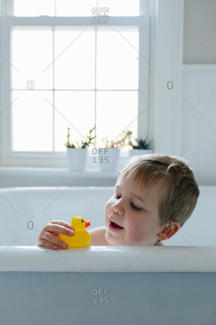 Boy sitting in a tub playing with a rubber duck