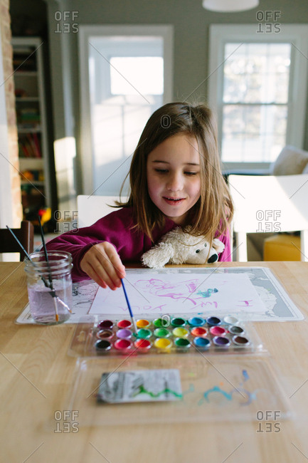 Little girl painting with watercolors at a dining table