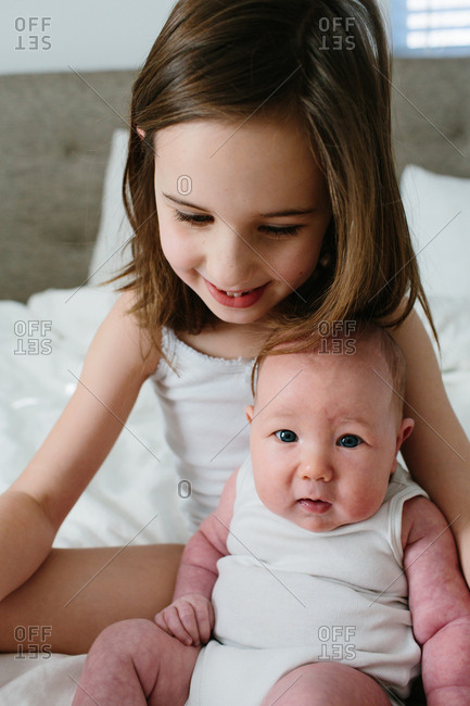 Little girl sitting on a bed with her infant sister in her arms