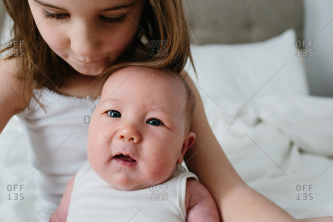 Little girl holding her infant sister in her arms on a bed