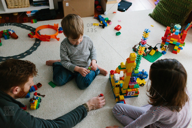 Father playing with building blocks with his son and daughter