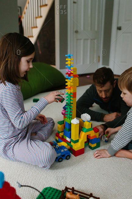 Father, son and daughter playing with building blocks on a floor