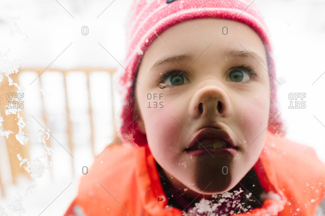 Little girl pressing her face against a window in the snow
