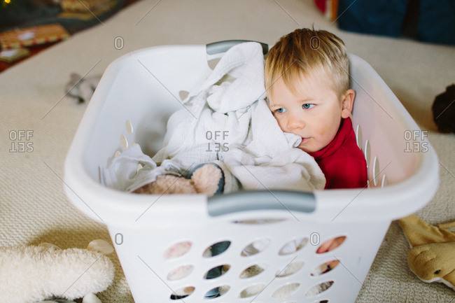 Little boy sitting in a laundry basket filled with clothes