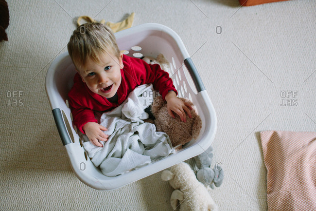 Little boy playing in a plastic clothes basket