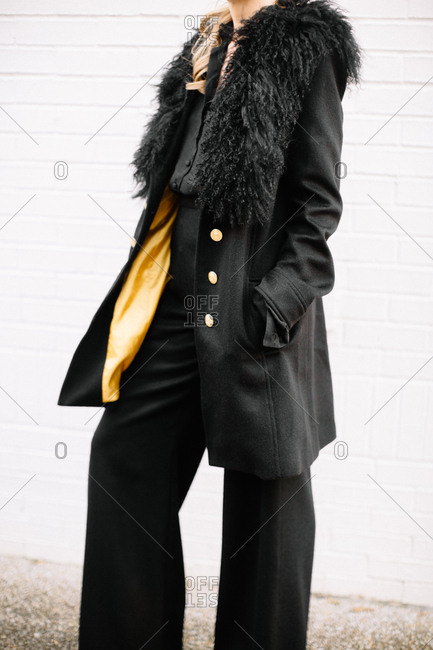 Woman in black high-waist pants and a stylish overcoat