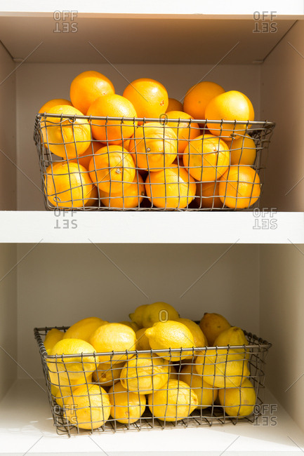 Lemons and oranges in wire baskets on a shelf