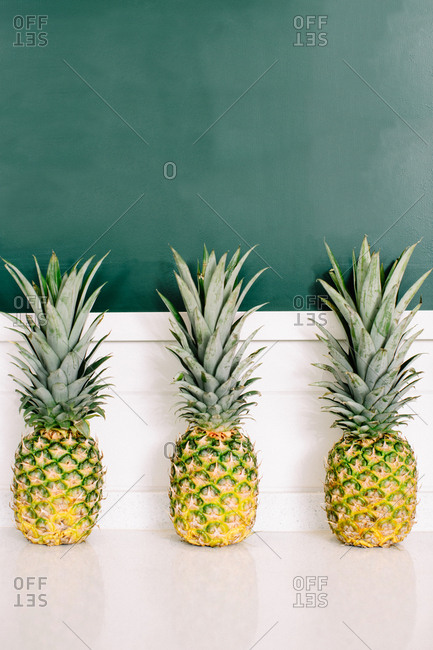 Three pineapples on a white countertop