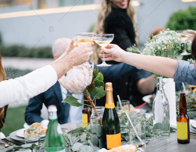 People making a toast at a stylish outdoor party
