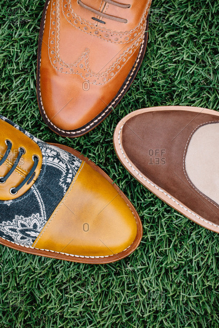 Three stylish men's leather shoes on grass