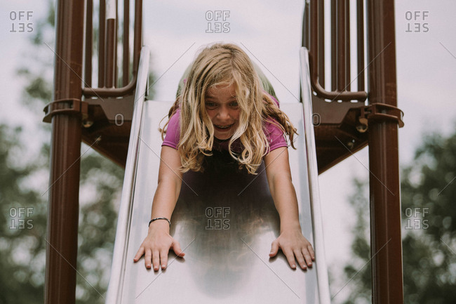 Little girl going down a slide head first