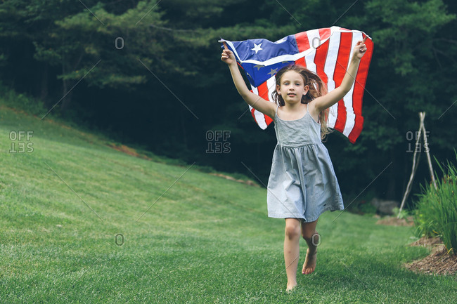 Little girl running on a lawn with an American flag over her head