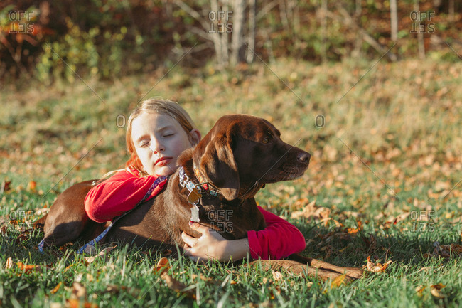 Little girl lying in a field hugging her dog