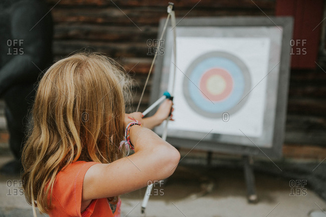 Little girl aiming a bow and arrow at an archery target