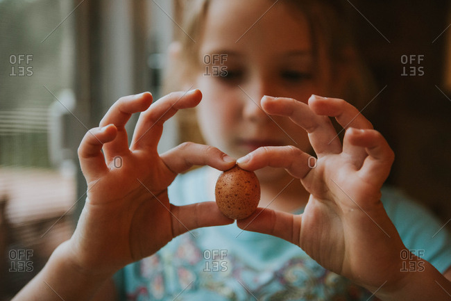 Little girl holding a small bird's egg between her two hands