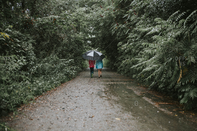 Two sisters walking under an umbrella on a wooded lane