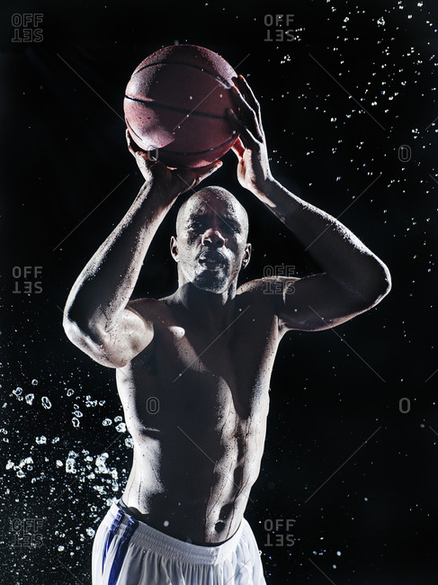 African American basketball player splashing in water