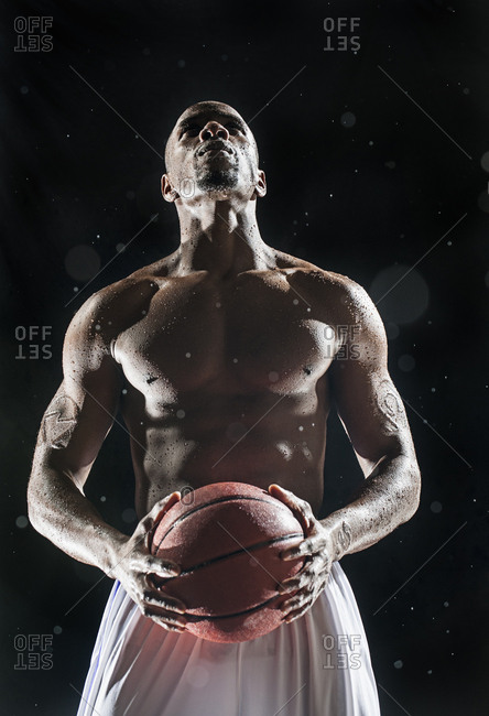 African American basketball player standing under lights