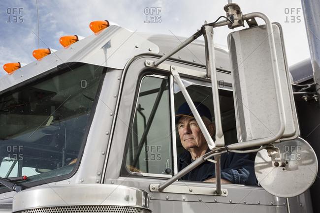 Caucasian trucker sitting in semi-truck