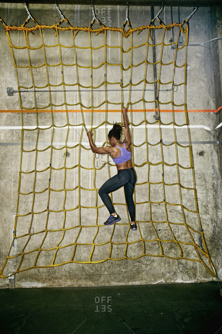 African American woman climbing net wall in gym