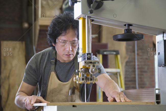 Asian carpenter using cutting machine in workshop