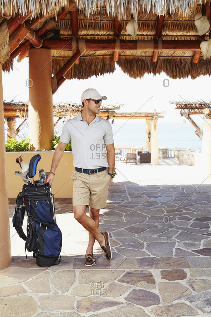 Mixed race man with golf clubs at hotel