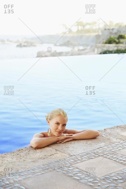 Caucasian woman relaxing in infinity pool