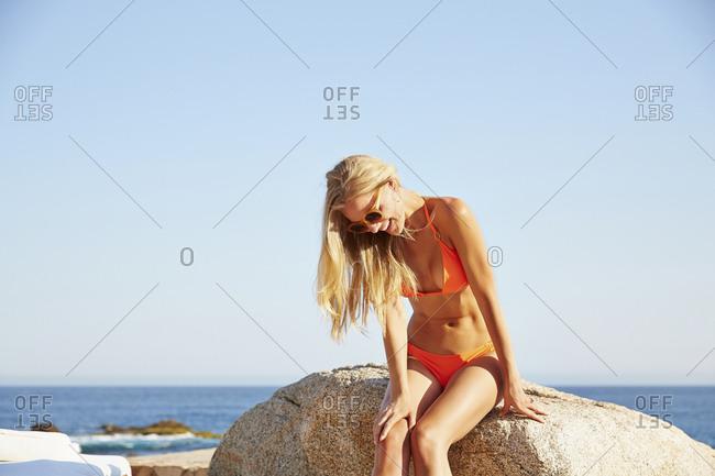 Caucasian woman sitting on rock on beach