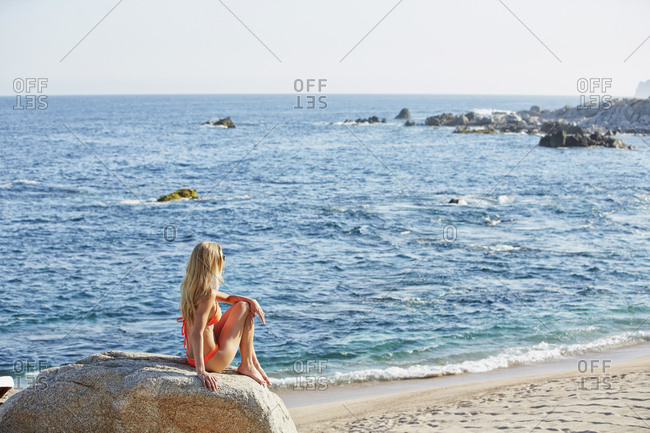Caucasian woman sitting on rock on beach