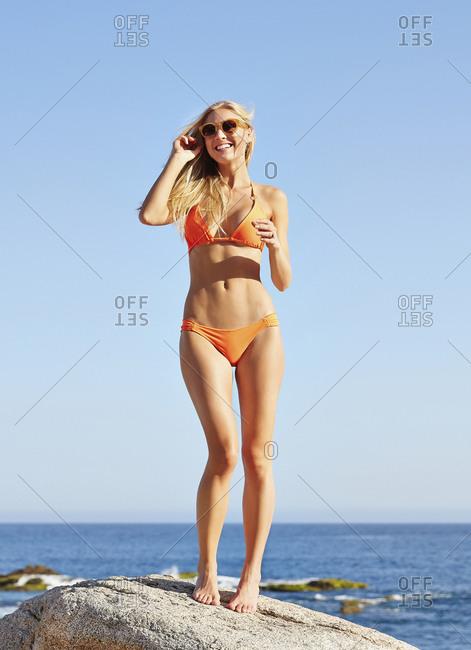 Caucasian woman standing on rock on beach