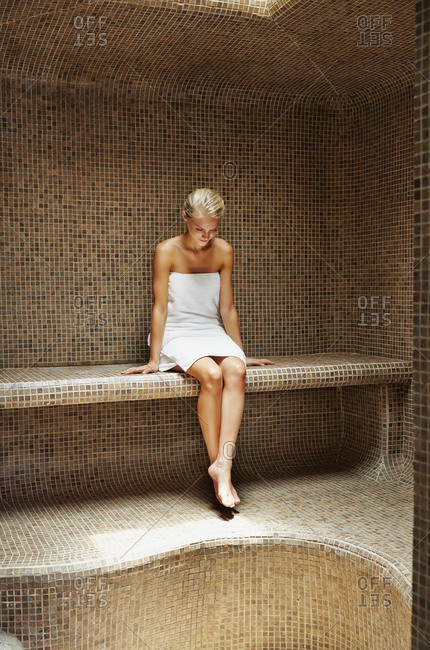 Caucasian woman relaxing in sauna