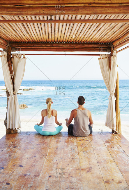Couple meditating together in cabana overlooking ocean