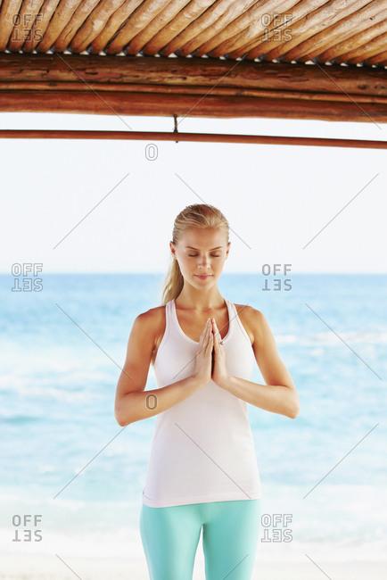 Caucasian woman meditating in cabana overlooking ocean