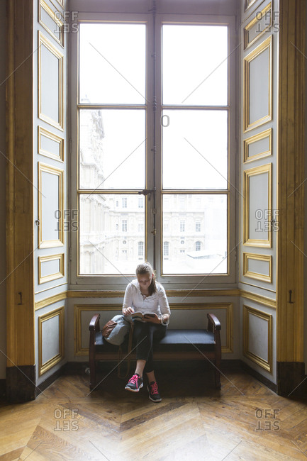 Caucasian teenage girl studying in ornate window at Louvre Museum, Paris, Ile De France, France