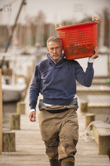 Caucasian fisherman carrying basket on dock