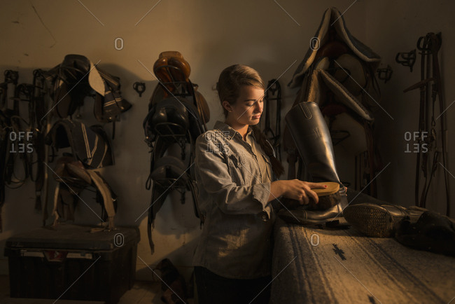Caucasian girl caring for boots in horse stable