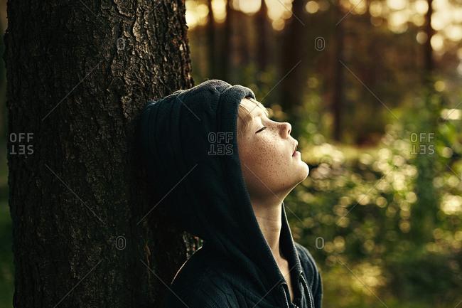 Caucasian boy leaning against tree