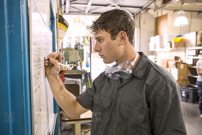 Caucasian worker writing on whiteboard in warehouse