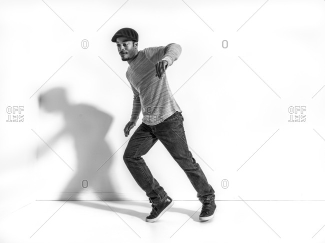 Black dancer casting shadow on wall